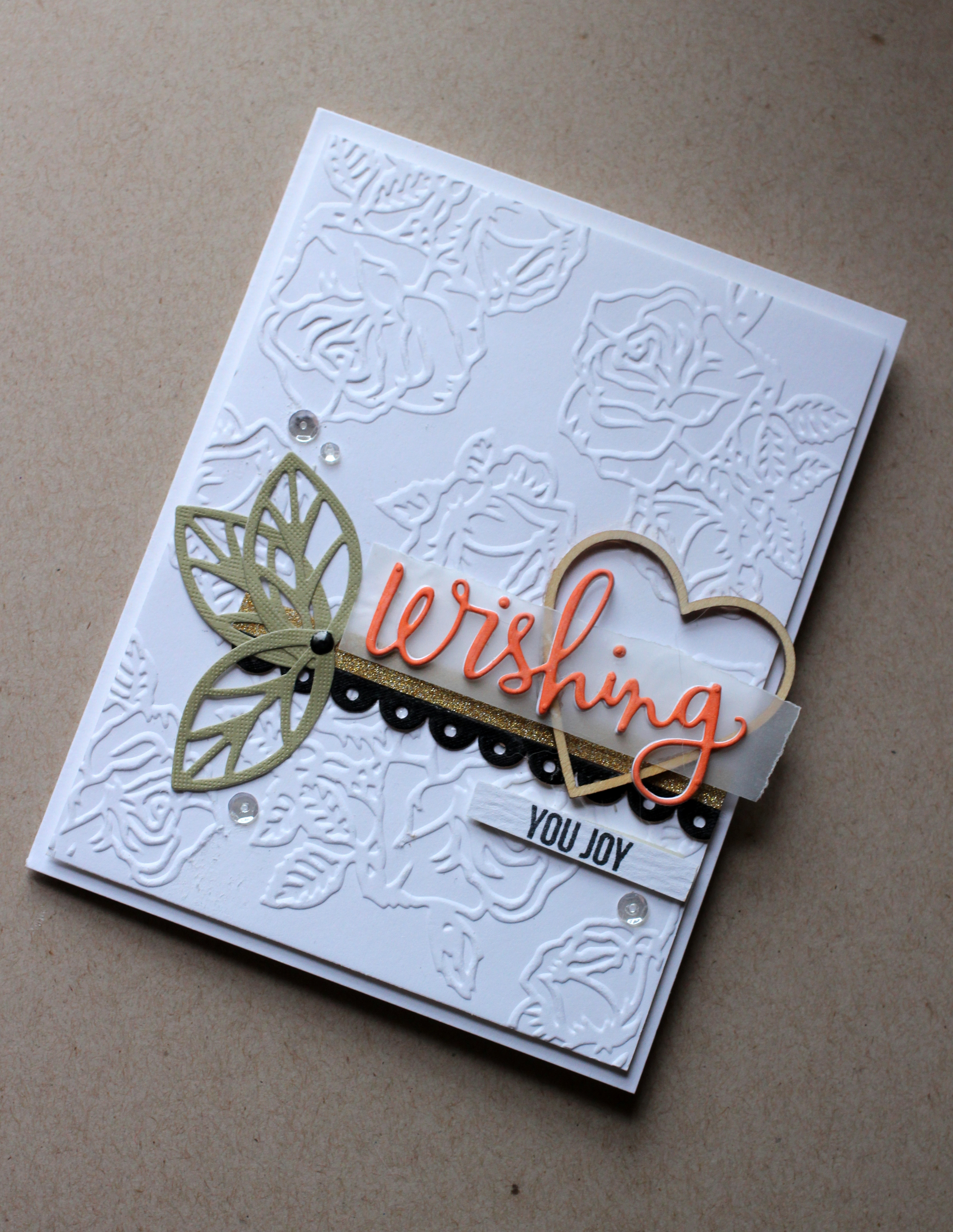 on the paper using an embossing folder a strip of black ribbon enamel dots a die cut sentiment washi tape vellum a wood veneer heart sequins